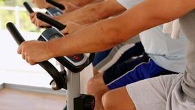 Three men working out on exercise bikes Stock Photo