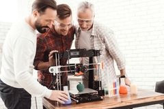 Three men are working to prepare printed on a 3d model printer. They stand three together around the 3d printert. Three men are working to prepare printed on a stock images