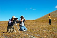 Three mens photographing a wonder of nature. Royalty Free Stock Photos