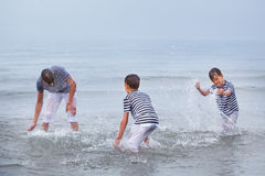 Three merry, happy, brother plays at sea Royalty Free Stock Photography