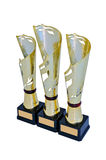 Three metal award cups of different height of gold color. With red detail for winners for the first second and third place are isolated on a white background royalty free stock photos