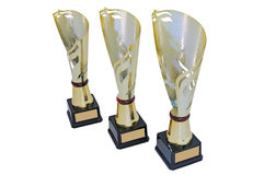 Three metal award cups of different height of gold color. With red detail for winners for the first second and third place are isolated on a white background royalty free stock photo