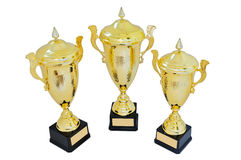 Three metal award cups of different height of gold color. For winners for the first second and third place are isolated on a white background royalty free stock photos