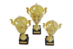 Three metal award cups of different height of gold color. For winners for the first second and third place are isolated on a white background. Top view royalty free stock photos