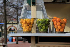 Three metal containers full of citrus fruit on outdoor shelving Stock Image