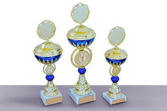 Three metal cups of gold color with blue details Stock Images