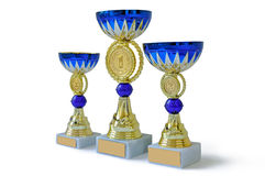 Three metal cups of gold color with blue details Royalty Free Stock Photo