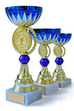 Three metal cups of gold color with blue details Royalty Free Stock Photos