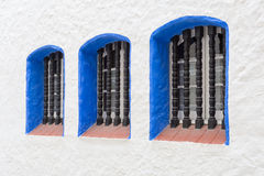 Three metal grilled windows with blue frames in mediterranean Sitges Royalty Free Stock Image