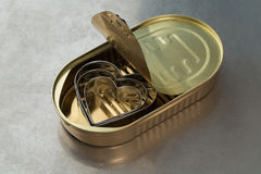 Three metal hearts in a tin Stock Image
