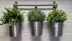 Three metal pots with green fake plants stock photography