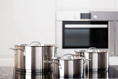 Three metal pots on induction hob Royalty Free Stock Image