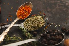 A lot of herbs and spices on dark old table. Three metal spoons with spices on dark old table or background. Dark moody photo. Selective focus Royalty Free Stock Photography