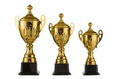 Three metal sports cups stand on a rank on a white background, gold cups Royalty Free Stock Photography