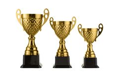 Three metal sports cups stand on a rank on a white background, gold cups Stock Photography