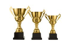 Three metal sports cups stand on a rank on a white background, gold cups Royalty Free Stock Photos