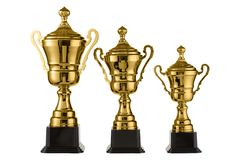 Three metal sports cups stand on a rank on a white background, gold cups Royalty Free Stock Photo