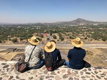 Three Mexican male tourists in straw hats sit with their backs to the camera on top of the pyramid against the backdrop of mountai. Ns and blue sky, back view stock photo