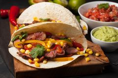 Three Mexican tacos with marbled beef, black Angus and vegetables on wooden Board on a dark stone background. Mexican dish with sa royalty free stock photography