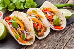 Three mexican tacos with meat and vegetables. Tacos al pastor on royalty free stock images