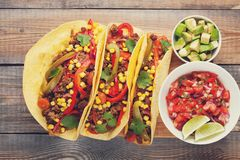 Three Mexican tacos with minced beef and mix vegetables on old rustic table. Mexican dish with sauce salsa in bowl and Royalty Free Stock Photos