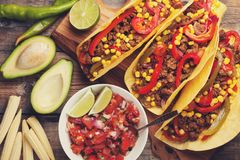Three Mexican tacos with minced beef and mix vegetables on old rustic table. Mexican dish with sauce salsa in bowl and Royalty Free Stock Photo