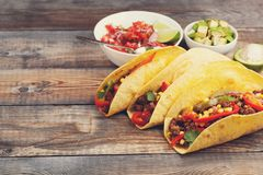 Three Mexican tacos with minced beef and mix vegetables on old rustic table. Mexican dish with sauce salsa in bowl and Royalty Free Stock Images