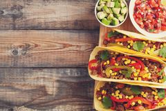 Three Mexican tacos with minced beef and mix vegetables on old rustic table. Mexican dish with sauce salsa in bowl and Stock Image