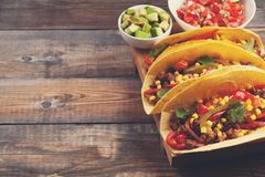 Three Mexican tacos with minced beef and mix vegetables on old rustic table. Mexican dish with sauce salsa in bowl and Royalty Free Stock Photography