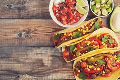 Three Mexican tacos with minced beef and mix vegetables on old rustic table. Mexican dish with sauce salsa in bowl and Royalty Free Stock Image