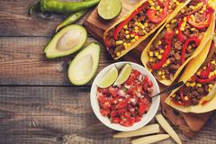 Three Mexican tacos with minced beef and mix vegetables on old rustic table. Mexican dish with sauces salsa in bowl and avocado. S Royalty Free Stock Image
