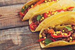 Three Mexican tacos with minced beef and mix vegetables on old rustic table. Mexican dish with sauces salsa in bowl and avocado. S Royalty Free Stock Photo