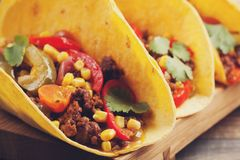 Three Mexican tacos with minced beef and mix vegetables on old rustic table. Mexican dish with sauces salsa in bowl and avocado. S Stock Photos