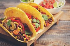 Three Mexican tacos with minced beef and mix vegetables on old rustic table. Mexican dish with sauces salsa in bowl and avocado. S Stock Photography