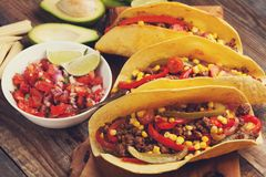 Three Mexican tacos with minced beef and mix vegetables on old rustic table. Mexican dish with sauces salsa in bowl and avocado. S Stock Images