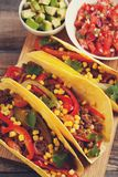 Three Mexican tacos with minced beef and mix vegetables on old rustic table. Mexican dish with sauces salsa in bowl and avocado. S. Picy and hot street food stock photos