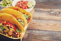 Three Mexican tacos with minced beef and mix vegetables on old rustic table. Mexican dish with sauce salsa in bowl and Stock Photos