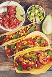 Three Mexican tacos with minced beef and mix vegetables on old rustic table. Mexican dish with sauce salsa in bowl and Stock Photo