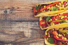 Three Mexican tacos with minced beef and mix vegetables on old rustic table. Mexican dish with sauces salsa in bowl and avocado. S Royalty Free Stock Images