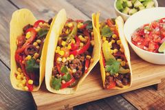 Three Mexican tacos with minced beef and mix vegetables on old rustic table. Mexican dish with sauces salsa in bowl and avocado. S Stock Image