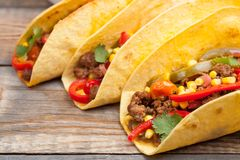 Three Mexican tacos with minced beef and mix vegetables on old rustic table. Mexican dish with sauces salsa in bowl and avocado. S Royalty Free Stock Photos