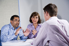 Three mid-adult people sitting at table meeting stock images