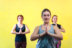 Three middle aged women practicing yoga in class. Portrait of three caucasian women practicing yoga, holding hands in namaste position. Body balance training royalty free stock photo