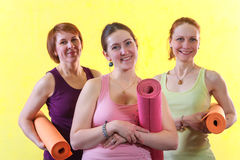 Three middle aged women after yoga session. Portrait of Three female adults after yoga session. Group of smiling middle aged caucasian women holding exercise stock photos