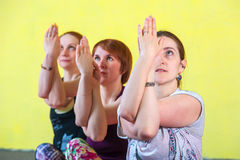 Three middle aged women in yoga session. Portrait of Three female adults practicing yoga in class. Group of caucasian women exercising on mats indoors, sitting stock photography
