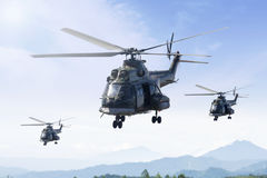 Three military helicopters patrolling in the mountain. Three military helicopters flying in the blue sky while patrolling in the mountain Royalty Free Stock Image