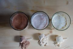 Three milk whey protein shakes in glass cups are arranged in a row with three scoops of protein on a wooden table. Top view three stock photography