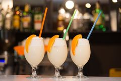 Three milkshakes with orange royalty free stock image