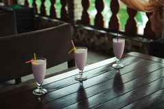 Three milkshakes and smoothies on wooden table royalty free stock image