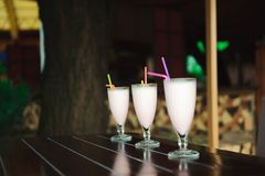 Three milkshakes and smoothies on wooden table. stock photos